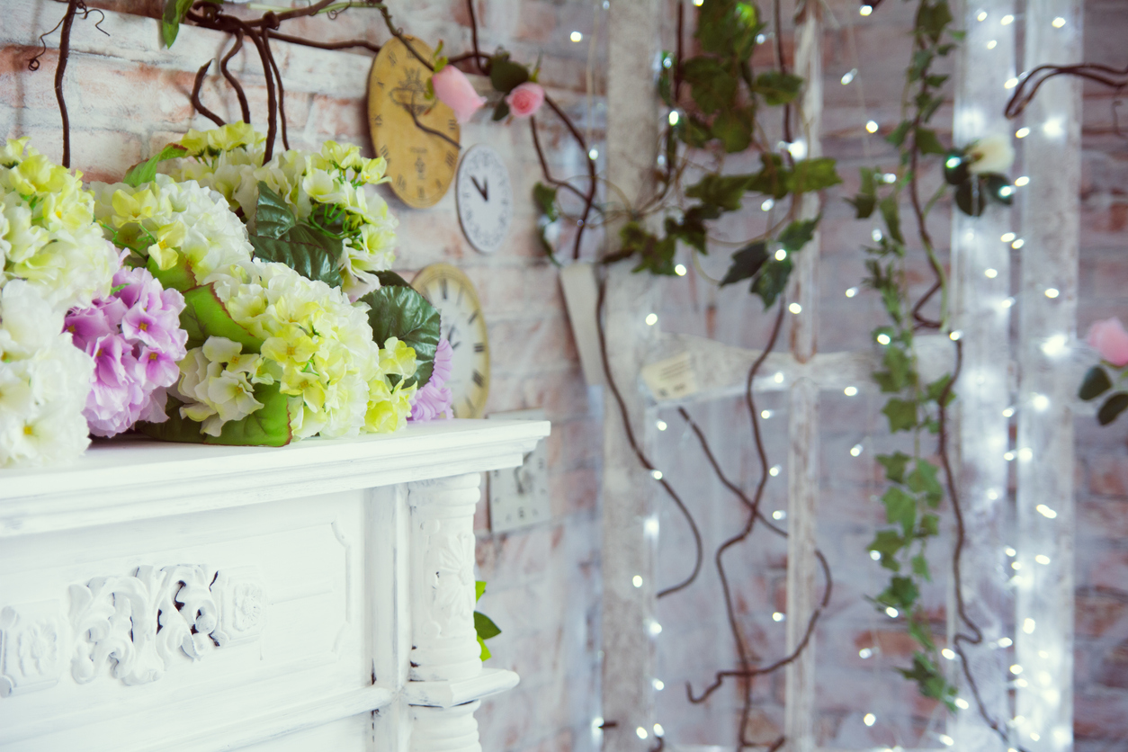 Decorative table with artificial flowers and a background of burning garlands
